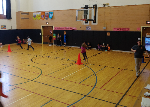 Students running in the gym at CES. Big screen to the right of photo.