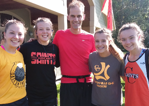Coach Strasser with members of girls' Varsity XC team