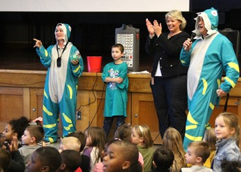 Teachers Brooke Elnicky and Greg Kincaid (in shark outfits) with CRS's student Heart Hero and Principal Kim Hale at the front of the auditorium.
