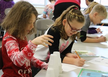 """Second-graders write simple code to instruct a """"robot"""" to pick up and place plastic cups in a preferred pattern."""