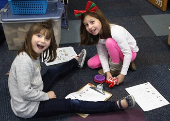 Two students laughing while working on a puzzle and sitting on the floor.