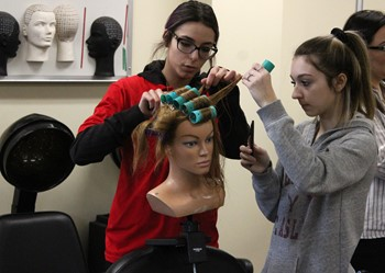CTE student demonstrating hair styling skills to CC student.
