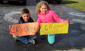 Two students holding signs in their driveway