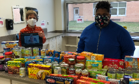 Students with stacks of food to be donated