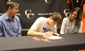 Caleb Smith signing his commitment letter to Daemen College while his parents look on