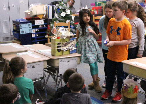Group of four students explaining to the class how their invention works