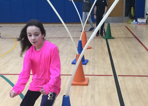 Student in gym running an obstacle course