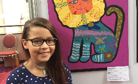 "Elizabeth Lessord (now in grade 3) with her oil pastel ""Wild Lion."""