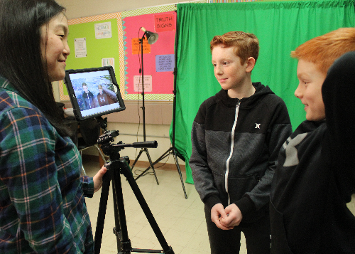 Two students reviewing their video public service announcement with librarian