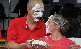 Principal Johnson and teacher Bethany Matsko with whipped cream pie on their faces