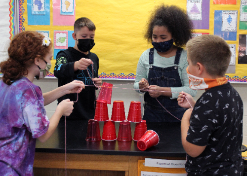 Four students building a pyramid with red cups and string