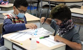 Two students programming their Ozobot robot