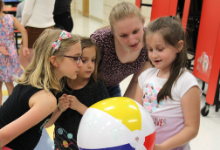 RIT student Allie Zeznick works on a getting-to-know-you activity with 3 second-graders