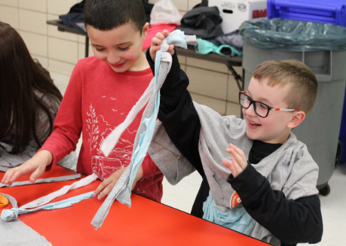 Two students working on making dog toys