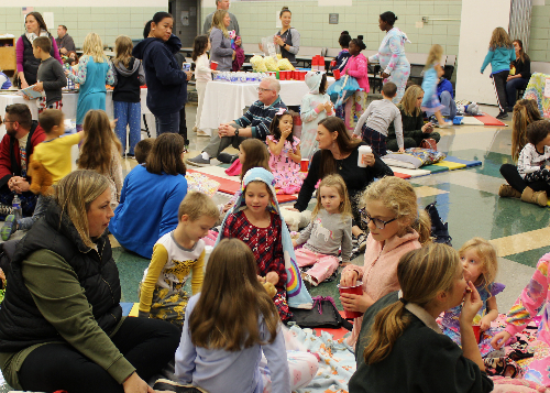 A cafeteria full of families and students sitting on mats in their pajamas and reading