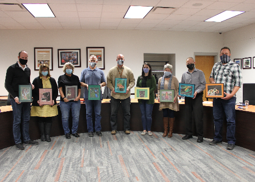 Board of Education members holding their gifted artwork