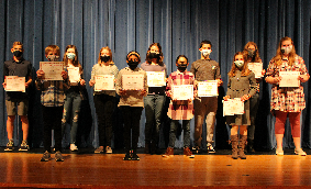 Triple C award winners holding certificates on the Middle School stage