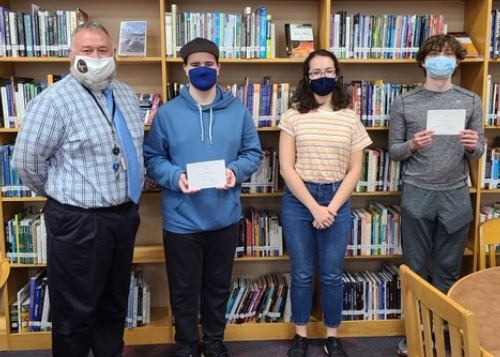 Principal Wilson with three honored students in the library