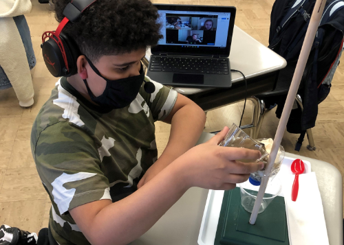 Student pouring muddy water through a water filter