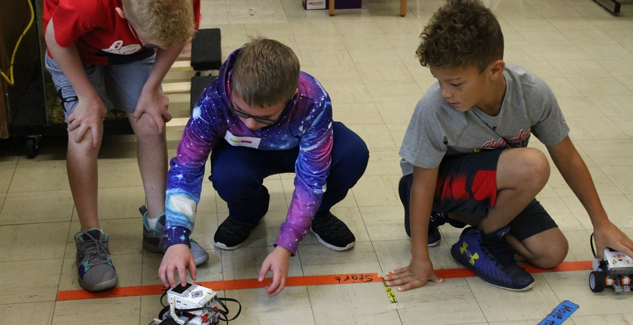 Three students programming a robot.