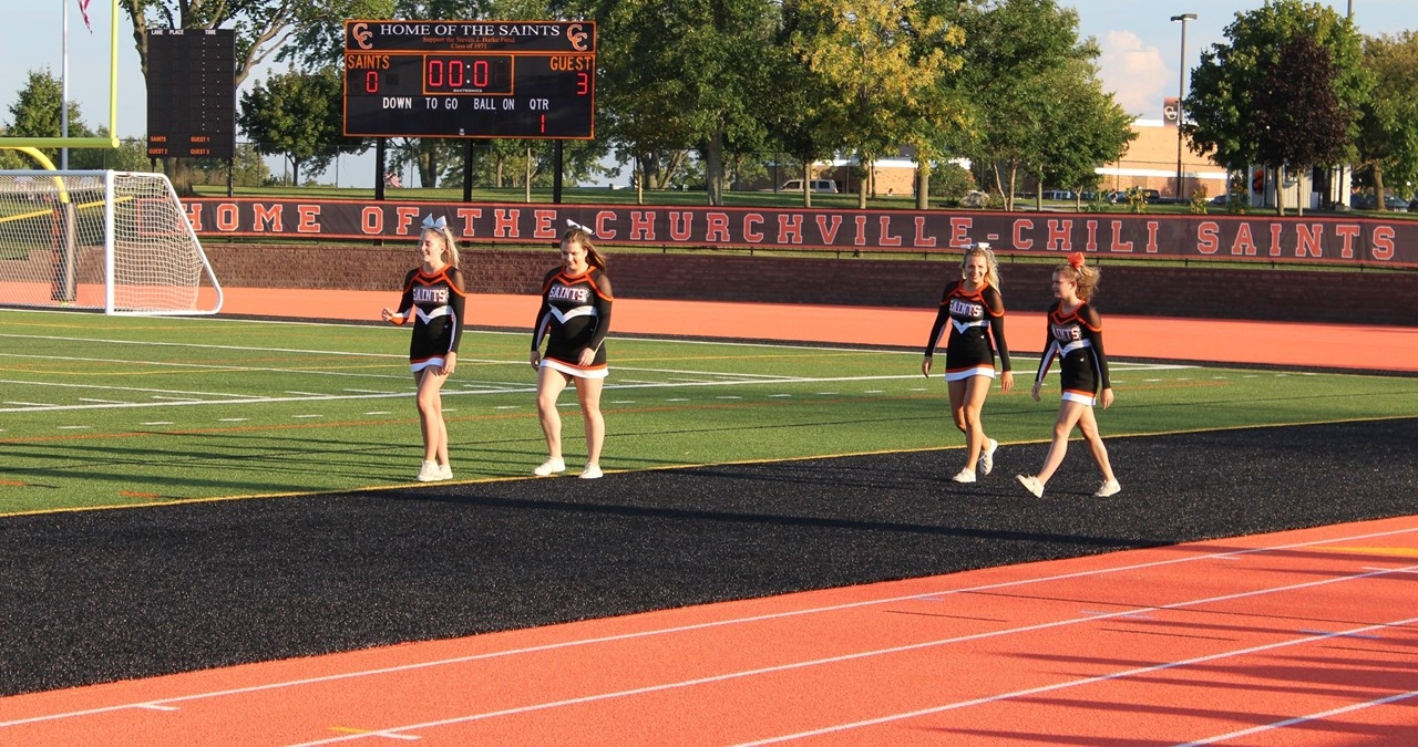 Cheerleaders walking on the field.