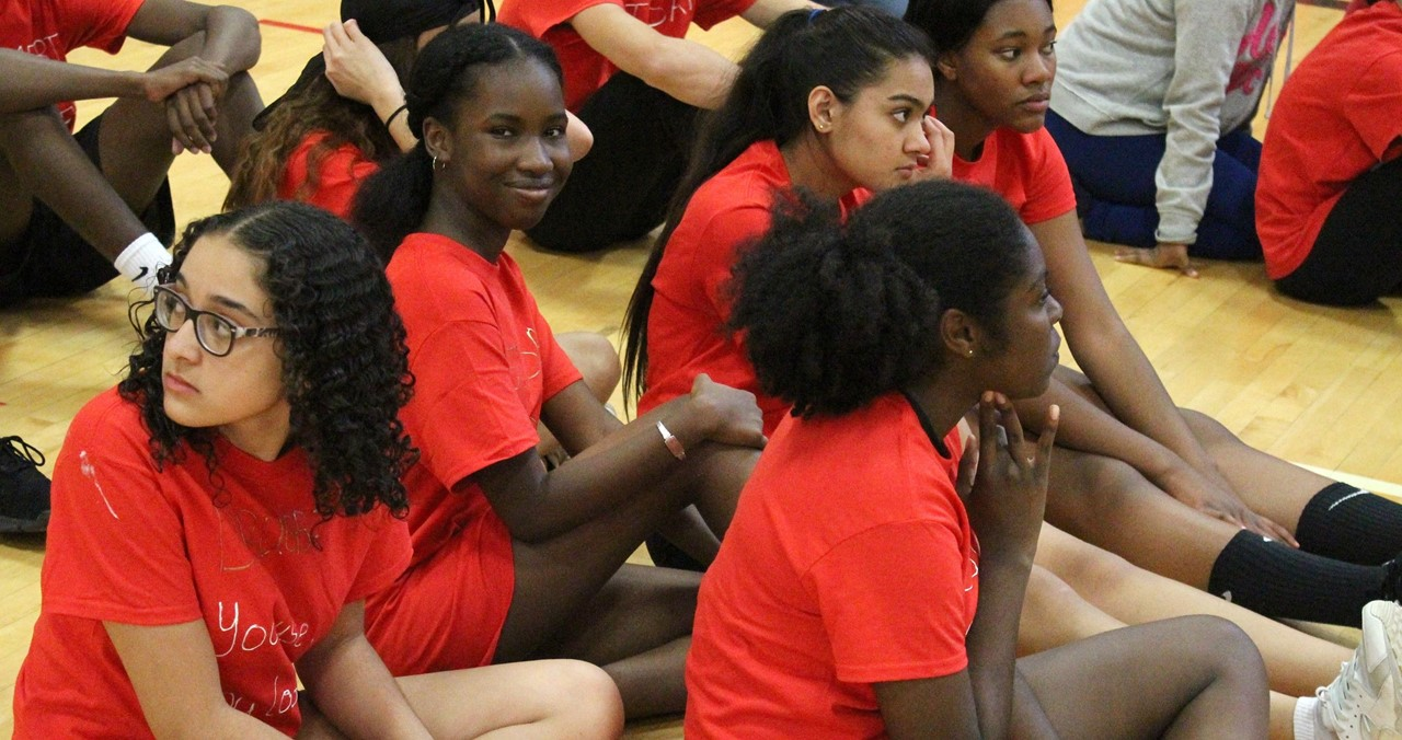 Group of students sitting on the floor during Red Ribbon Volleyball event.