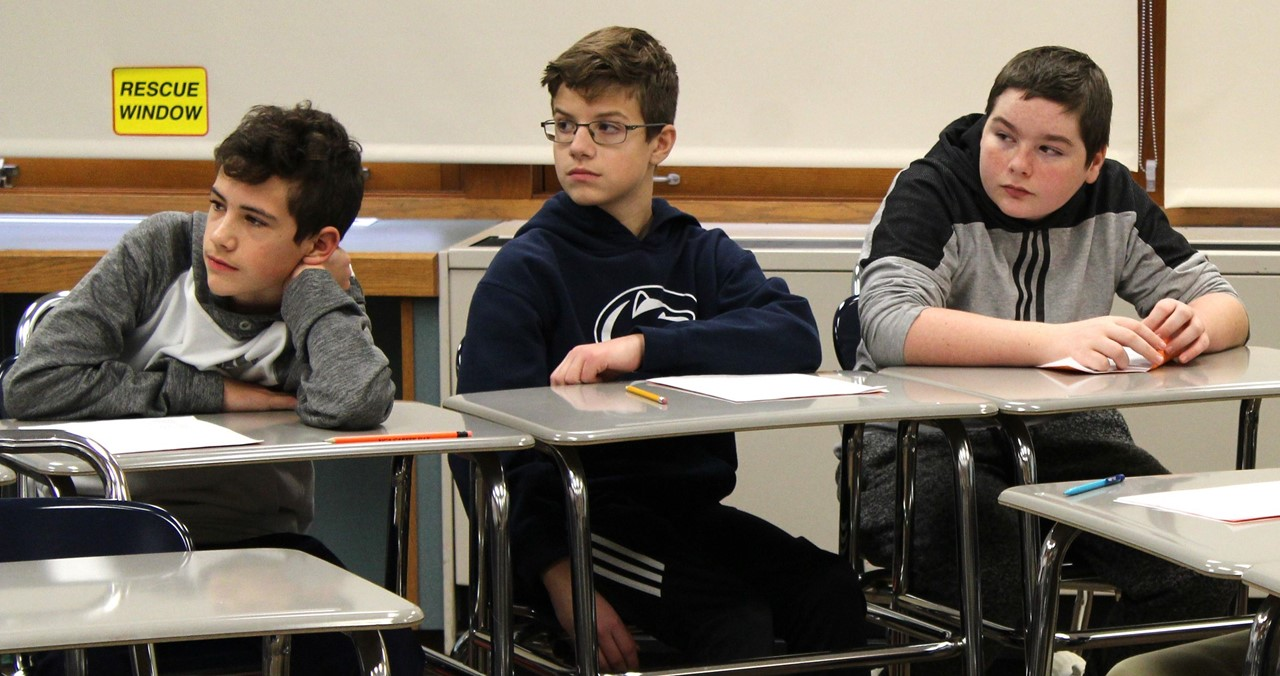 Three students sitting at their desks listening.