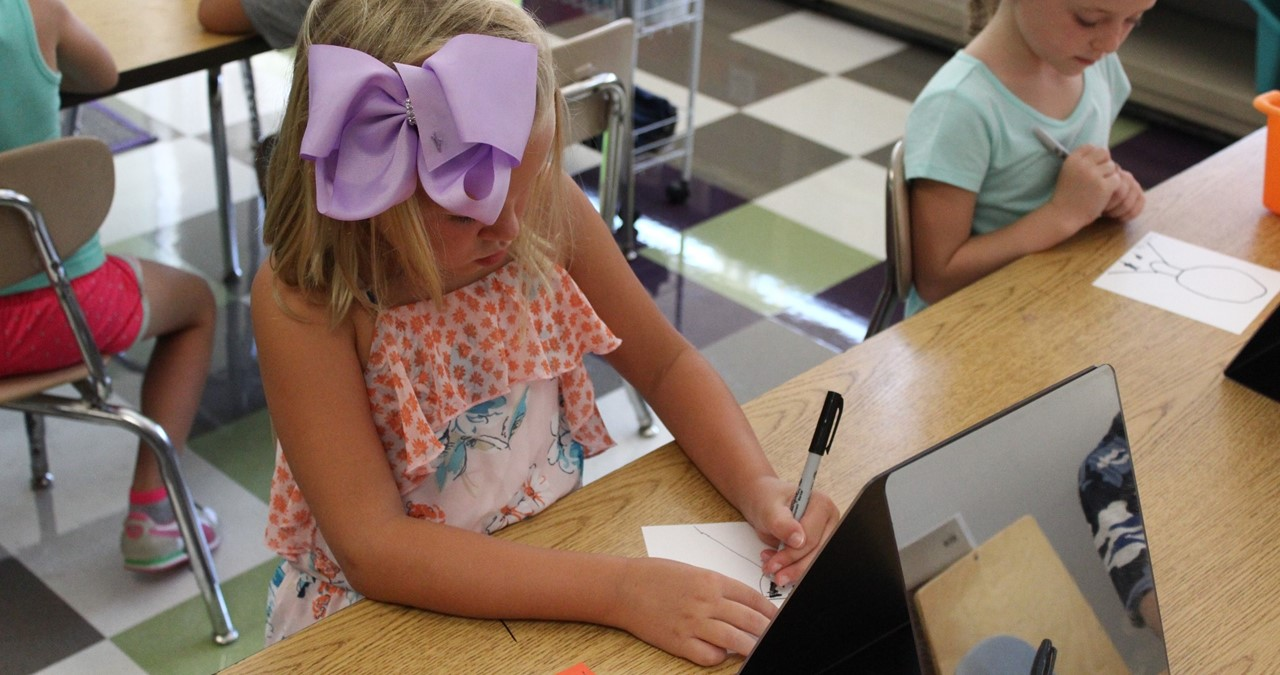 CRS student wearing large purple hairbow in art class.