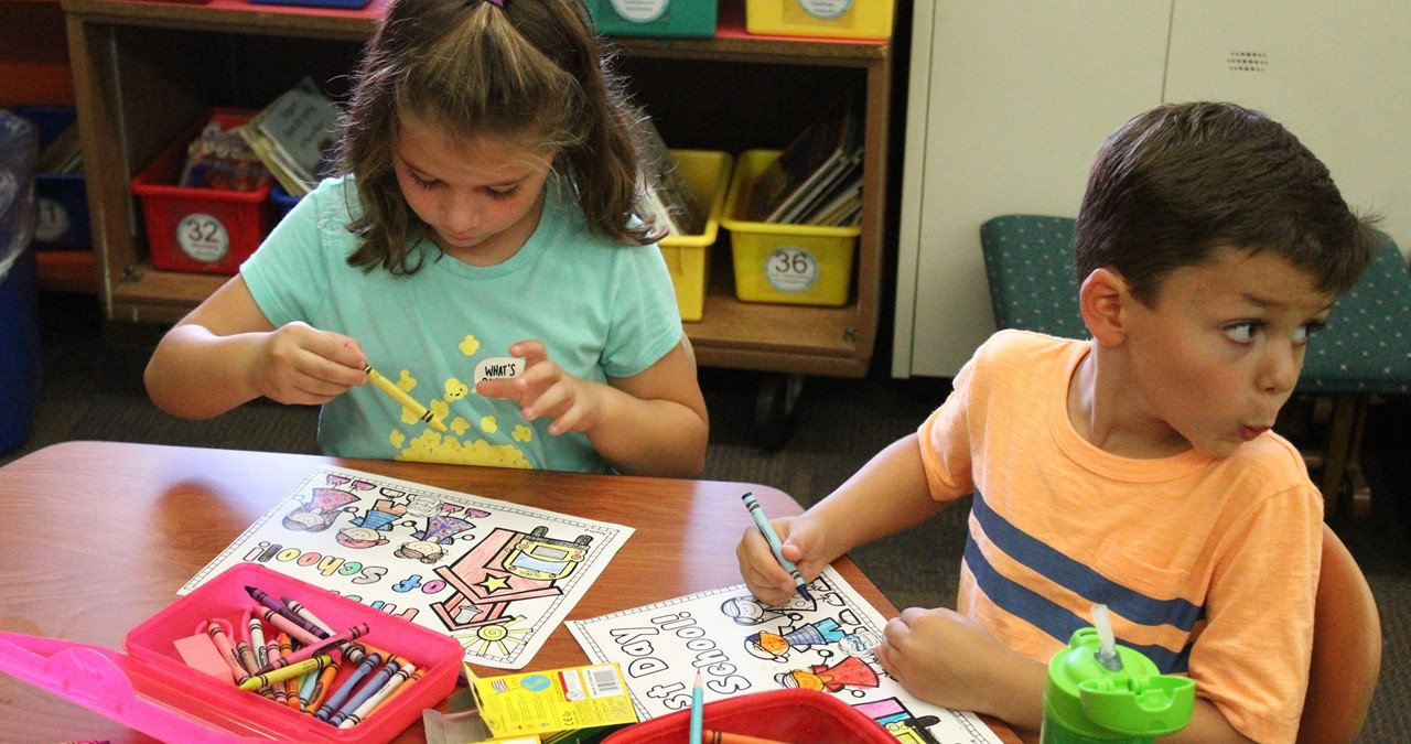 Two students coloring at their desk.