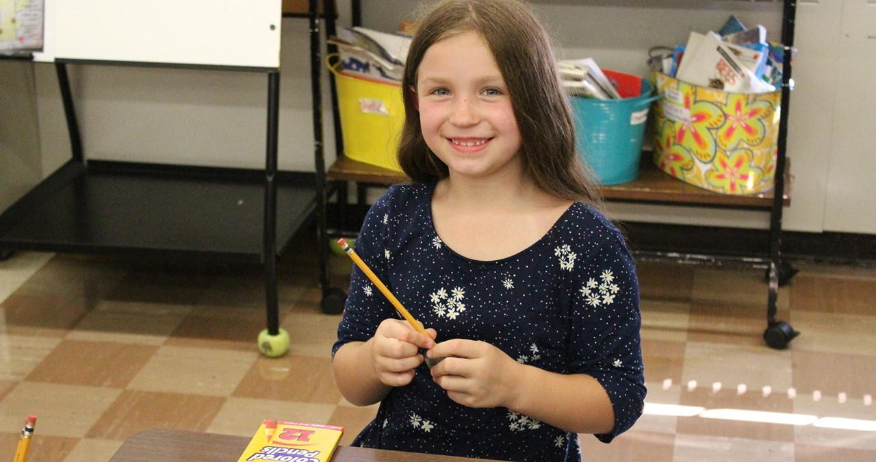 Closeup of smiling student holding pencil.