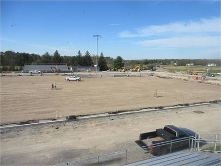 Construction workers and vehicles working on athletic field