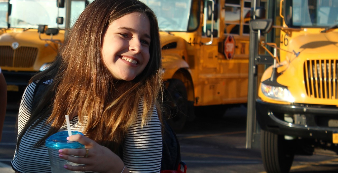 Smiling student holding a cup in front of buses.