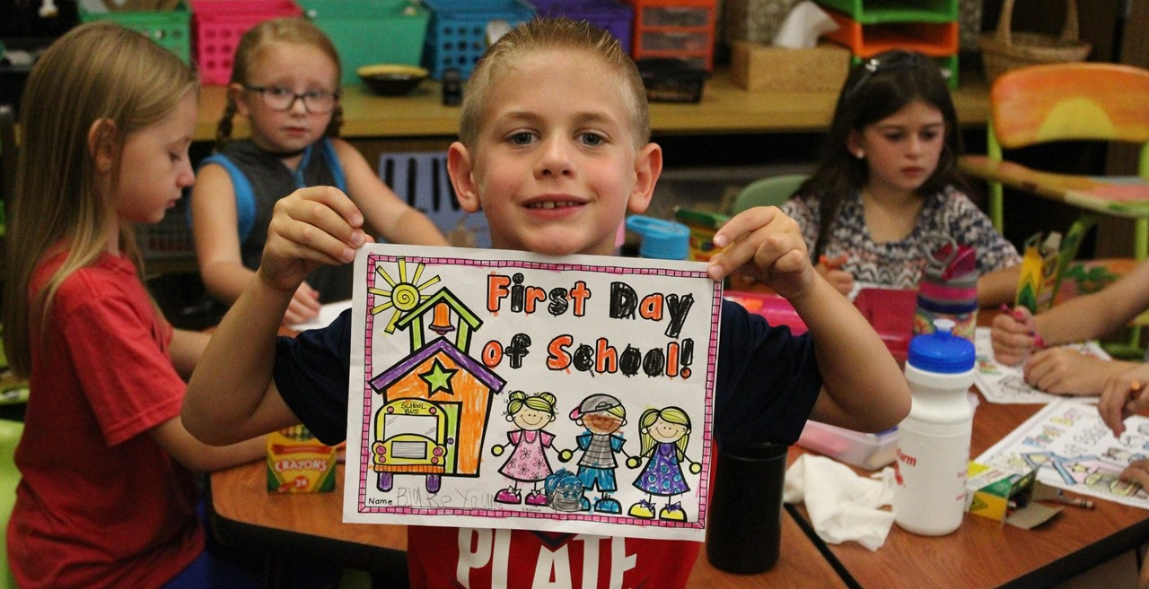 """Student holding """"First Day of School"""" artwork."""