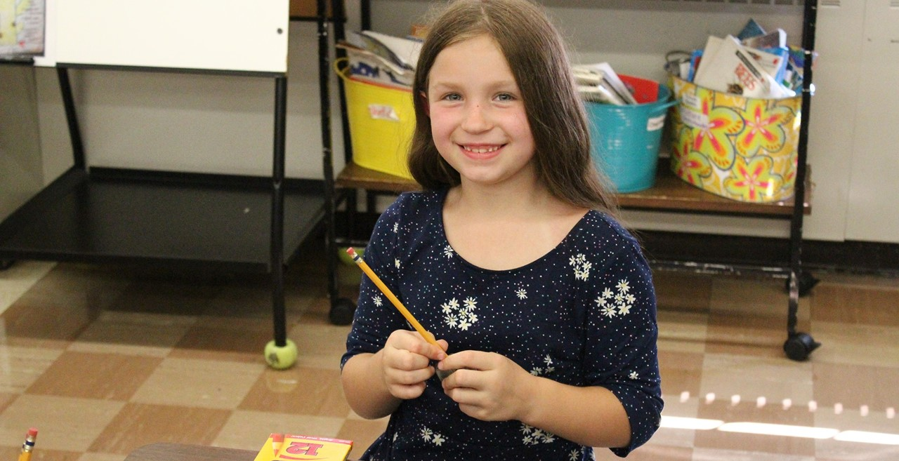 Smiling student with pencil.