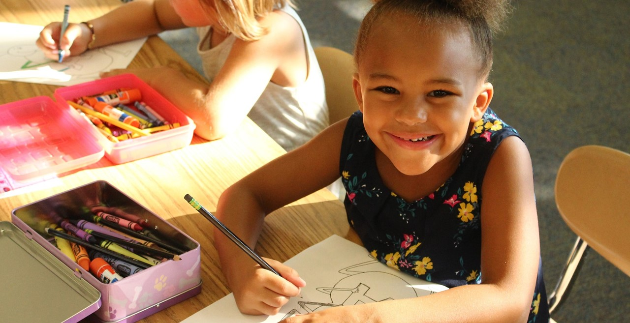 Smiling student with crayons.