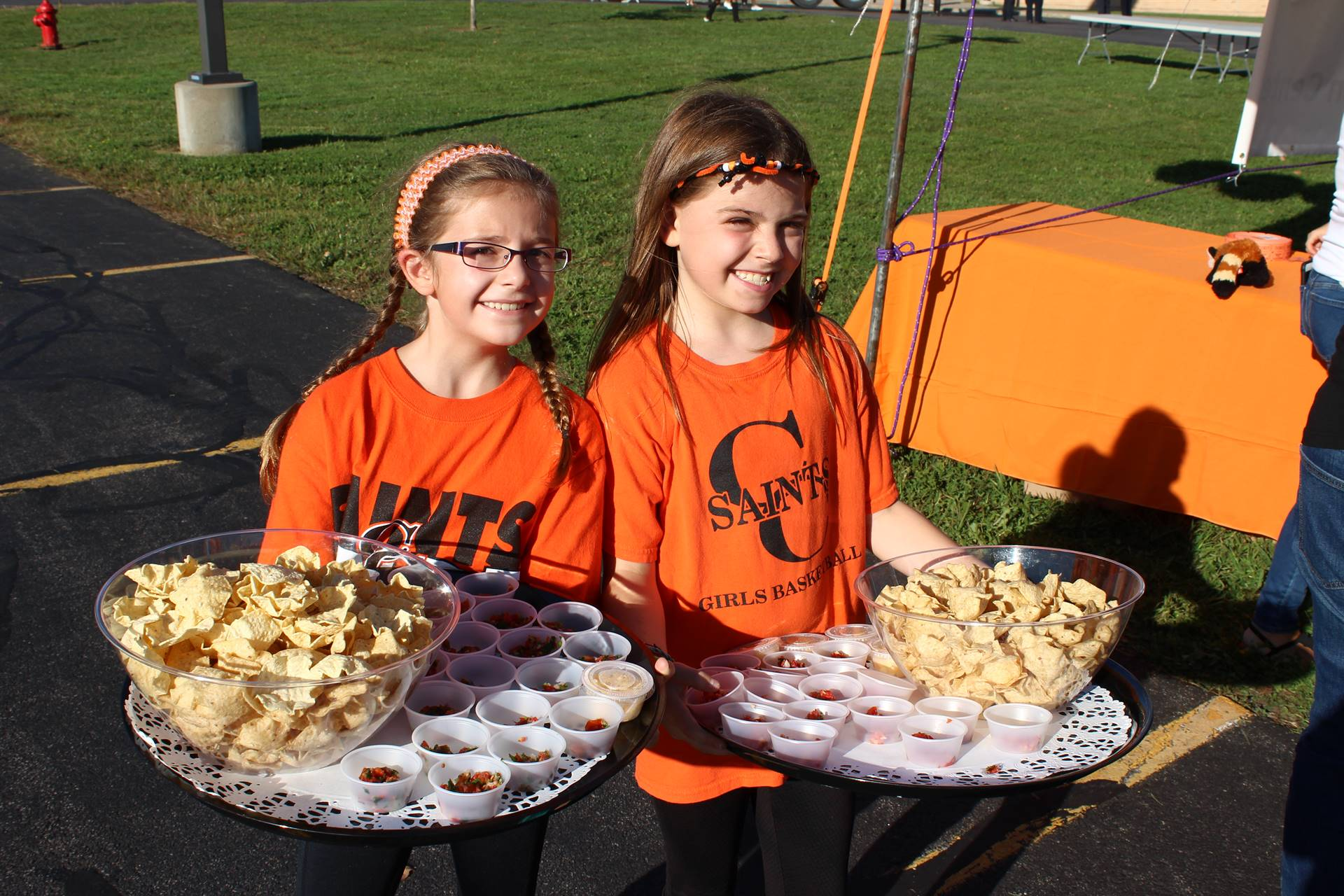 Two young students serving chips and salsa.