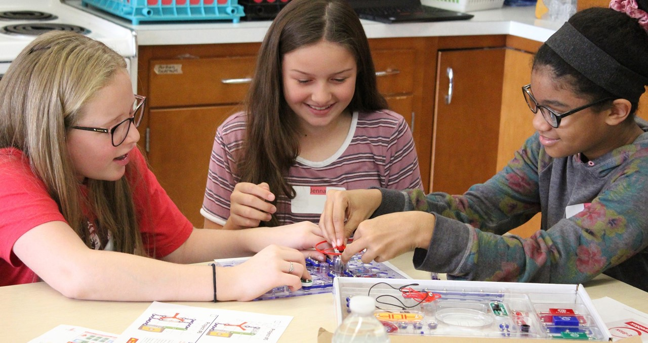 Three students creating electrical circuits