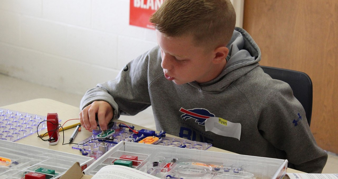 Student in grey sweatshirt working with electrical circuits