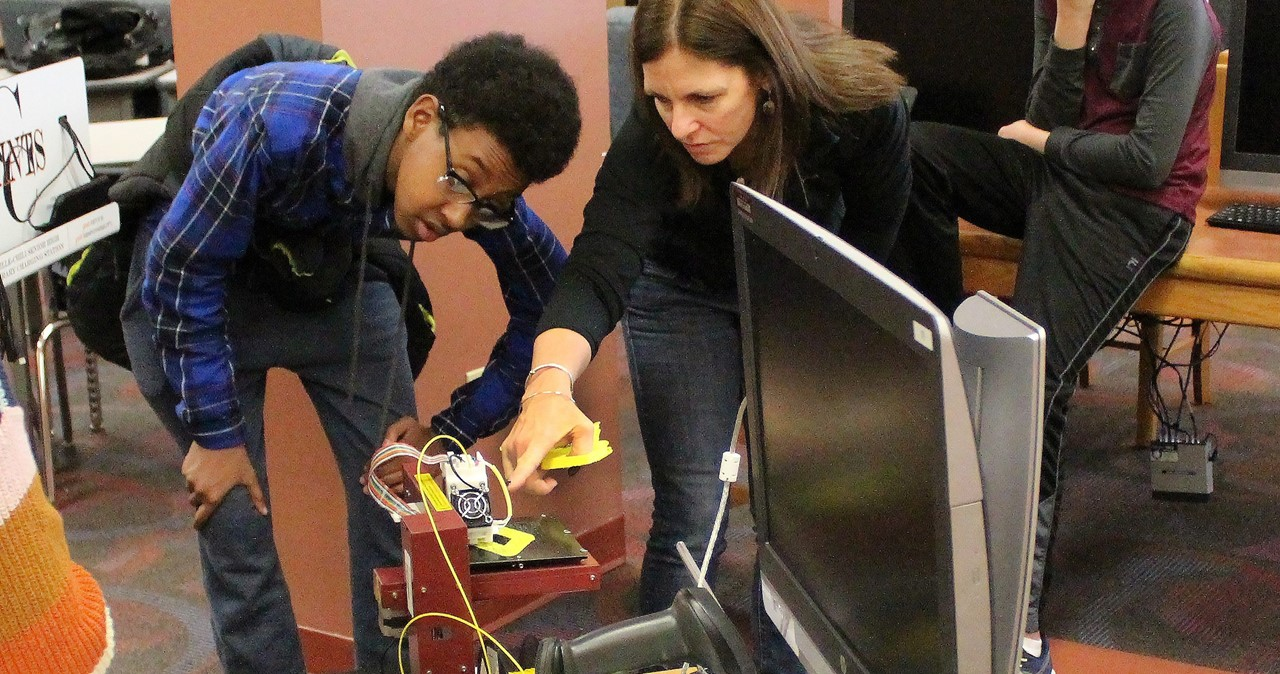 Teacher and student examining a 3-D printer in the library