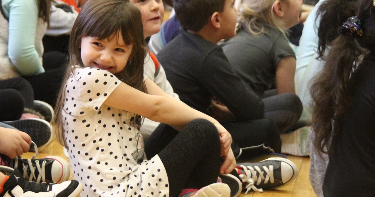 Smiling student in polka dot dress sitting on the floor.