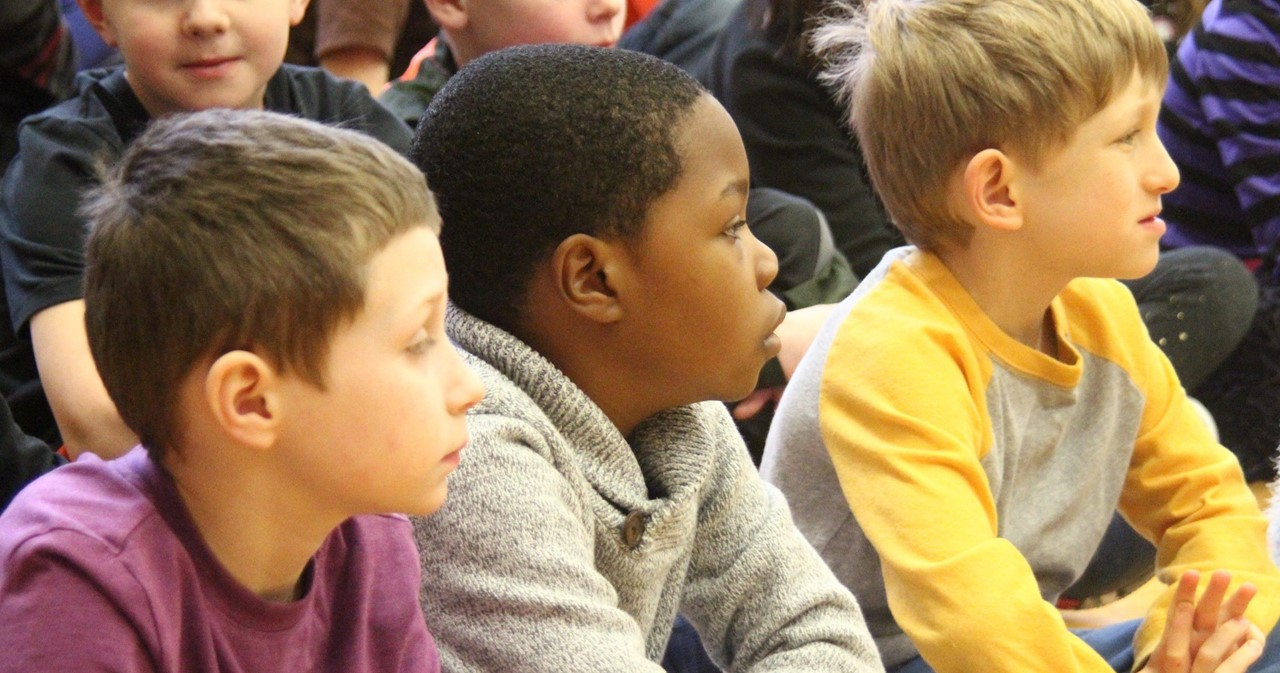 Three students listening at an assembly.