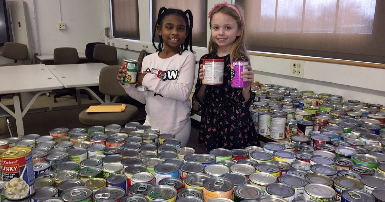 Two students with cans collected for Canstruction project.