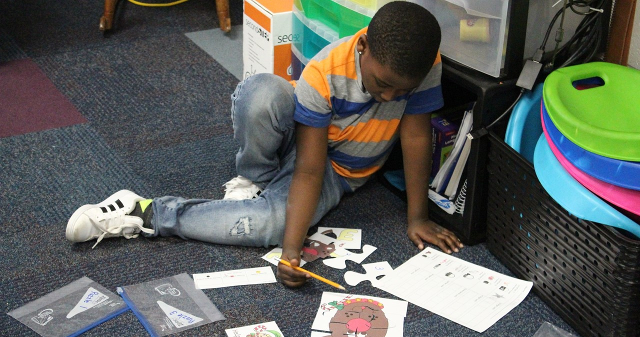 CRS student working out a math puzzle on the floor.
