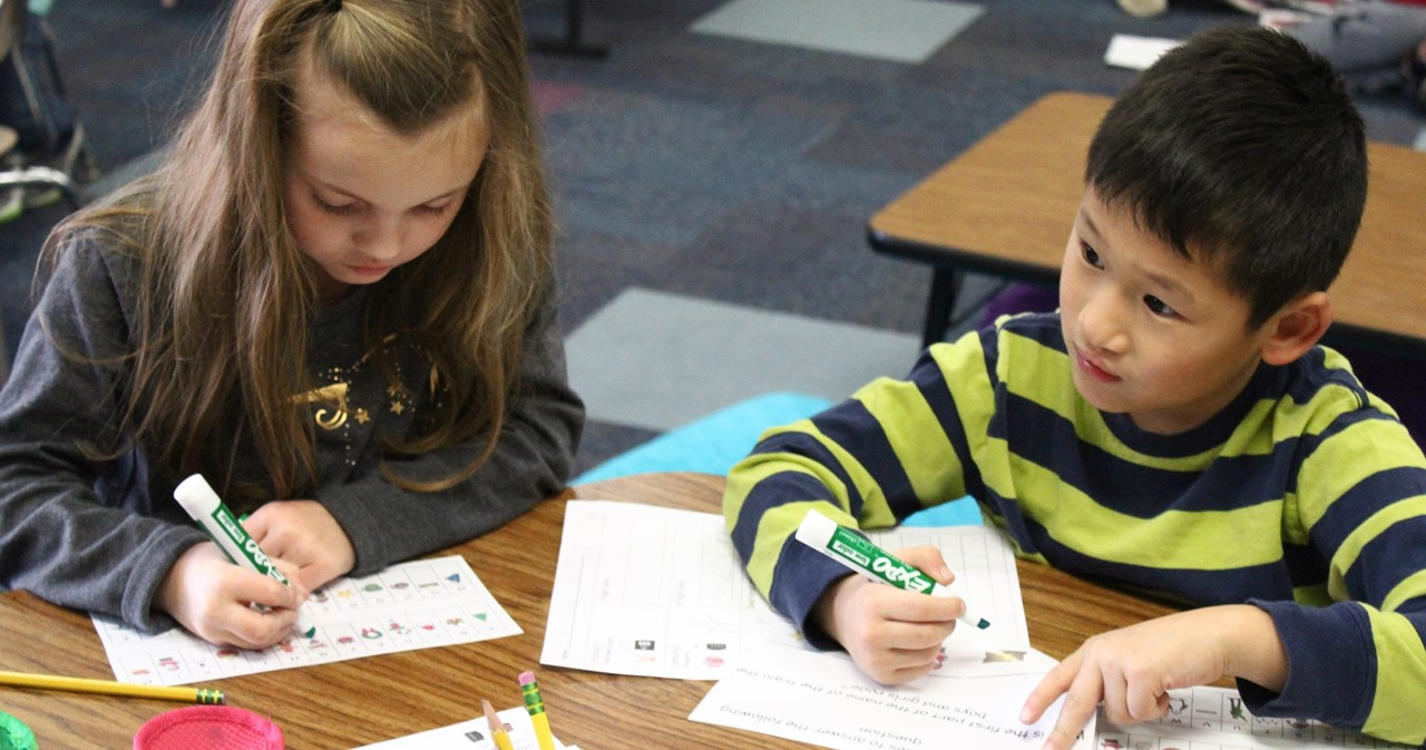 Two students working on math puzzles at a table.