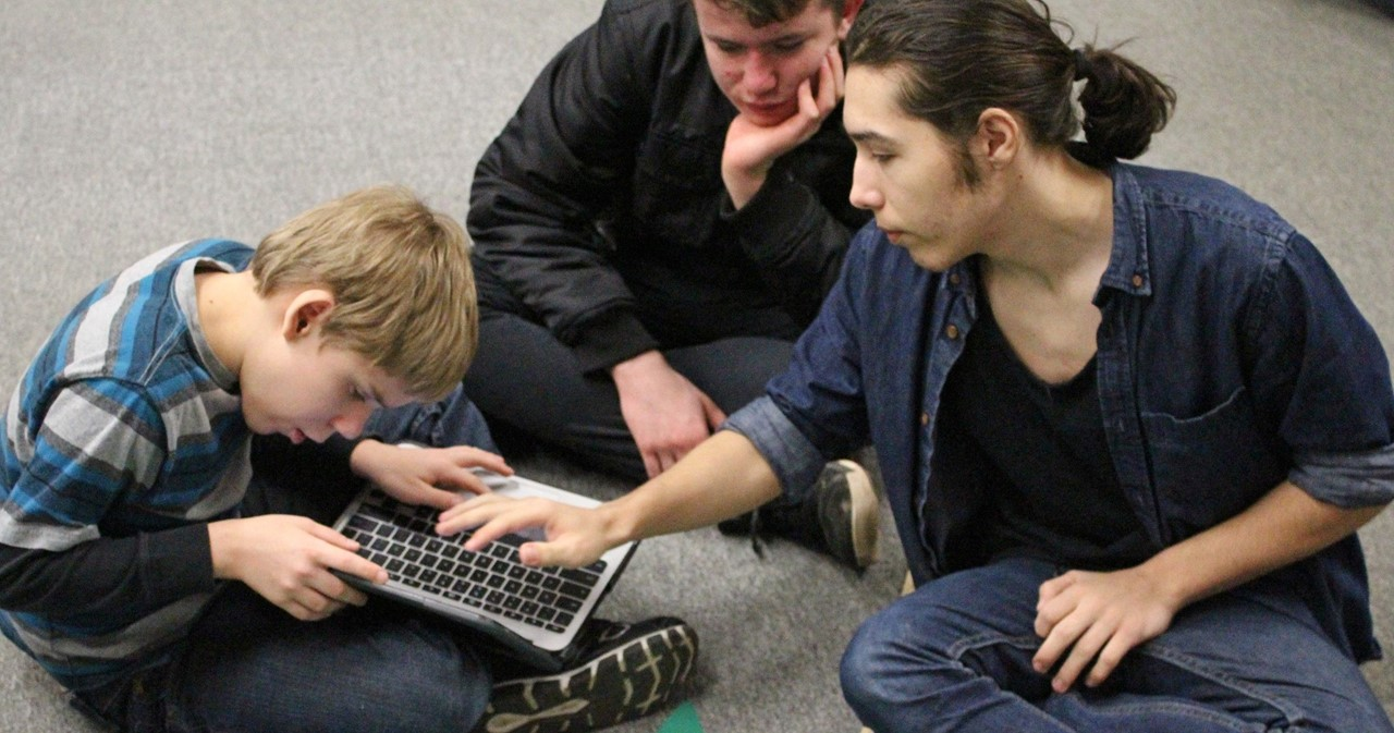 Three NGA students programming a robot.