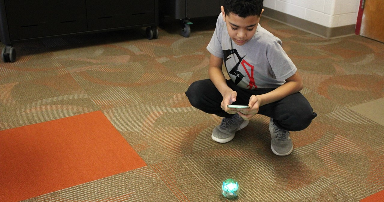 MS student programming a Sphero robot in the library.