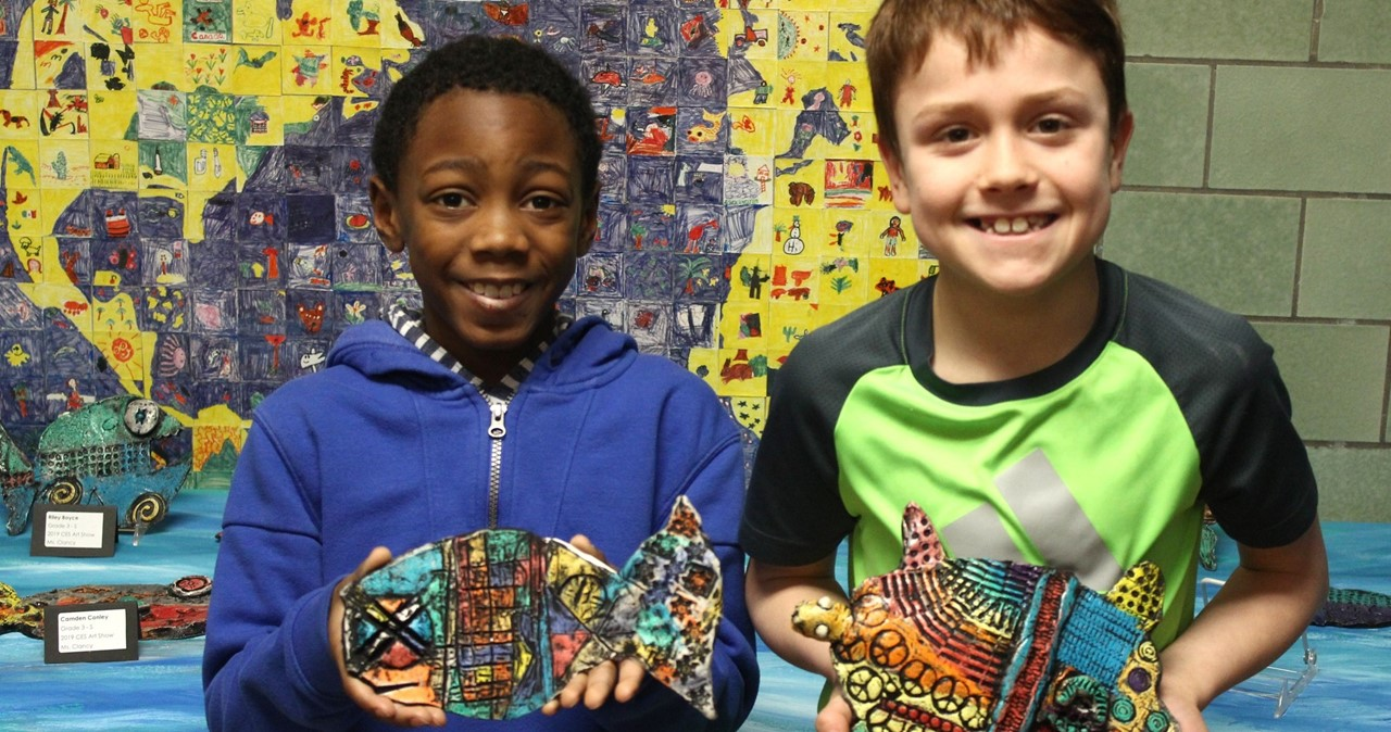 Two students with their ceramic fish.
