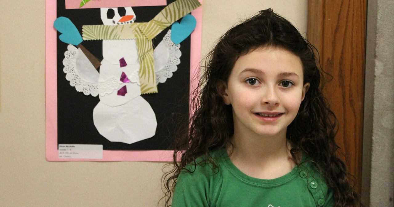 Student with artwork of snowman.