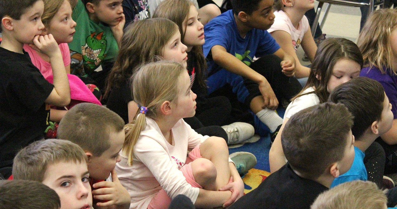 Group of second-graders listening to guest speaker.