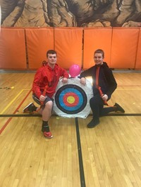 2 Students next to Archery target after winning the balloon challenge